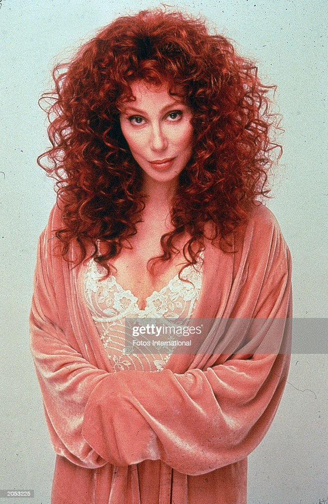 Portrait of American singer and actor Cher wearing a pink satin robe over a white lace bustier, circa 1992.
