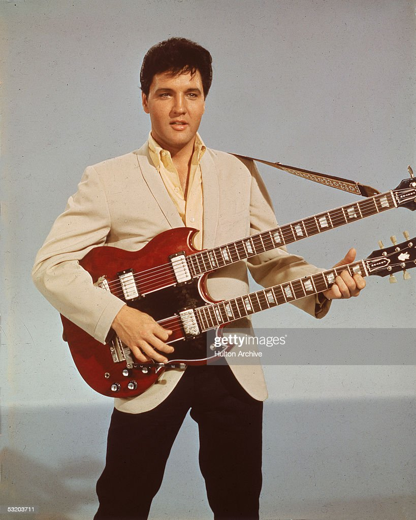 Portrait of American singer and actor Elvis Presley as he holds a twelve string guitar mid 1950s