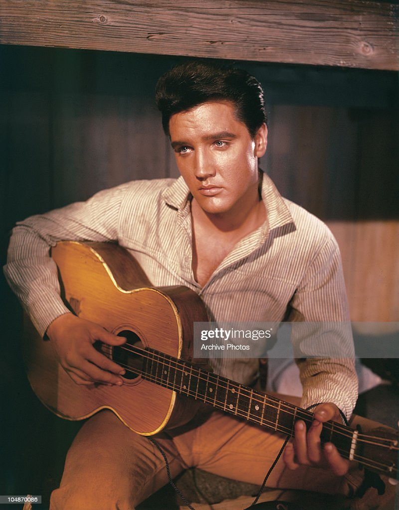 A portrait of American singer and actor Elvis Presley holding an acoustic guitar circa 1956