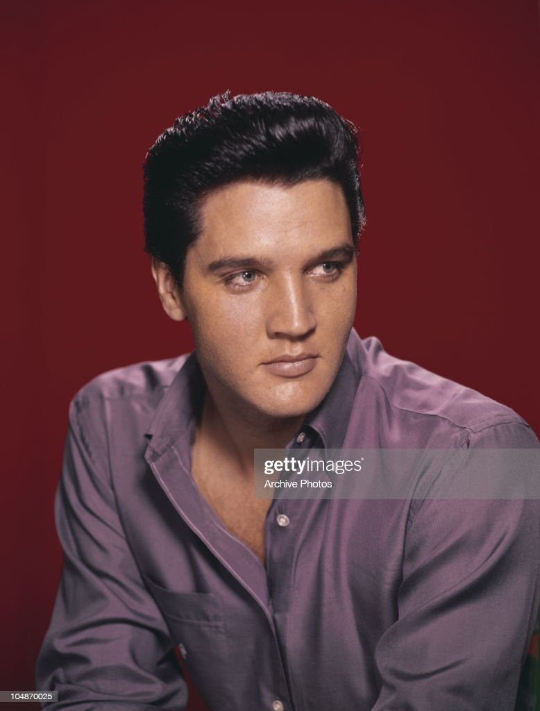 A portrait of American singer and actor Elvis Presley wearing a purple shirt circa 1956