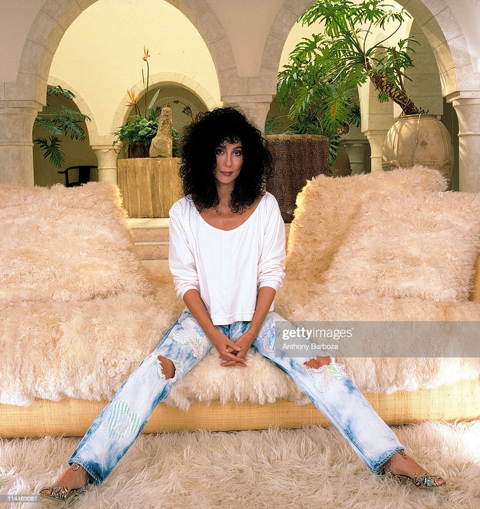Portrait of American singer and actress Cher as she sits on a very fuzzy couch dressed in a sweatshirt, jeans, and high heels, Los Angeles, California, 1987.