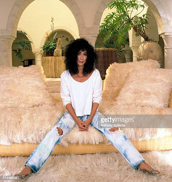 Portrait of American singer and actress Cher as she sits on a very fuzzy couch dressed in a sweatshirt jeans and high heels Los Angeles California...