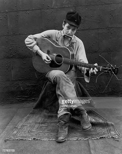 Portrait of American singer and musician Bob Dylan as he sits in a chair and plays his guitar and harmonica New York New York 1962