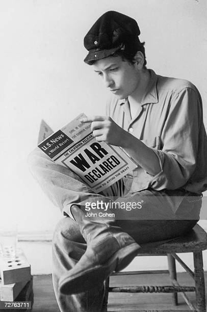 Portrait of American singer and musician Bob Dylan as he sits on a chair next to a pile of bricks and reads a copy of the US News and World Report...