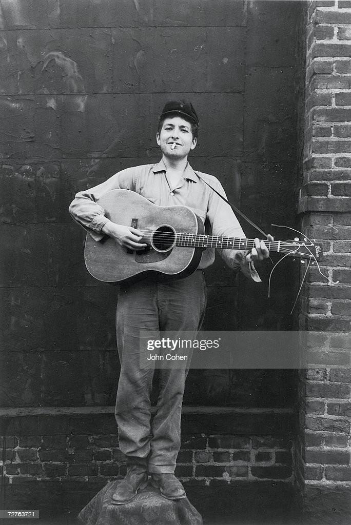 Portrait of American singer and musician <a gi-track='captionPersonalityLinkClicked' href=/galleries/search?phrase=Bob+Dylan&family=editorial&specificpeople=203289 ng-click='$event.stopPropagation()'>Bob Dylan</a> (born Robert Zimmerman) as he stands on a chair, a guitar in his hands, a cigarette in his mouth, and a smile on his face, New York, New York, 1962.