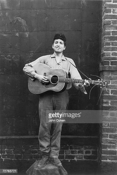 Portrait of American singer and musician Bob Dylan as he stands on a chair a guitar in his hands a cigarette in his mouth and a smile on his face New...