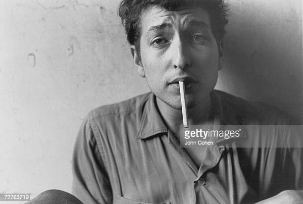 Portrait of American singer and musician Bob Dylan with a crinkled brow and an unlit cigarette in his mouth New York New York 1962