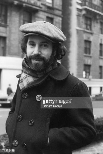 Portrait of American singer and musician Paul Simon as he stands on a sidewalk hands his the pockets of his pea coat and a cap on his head 1970s