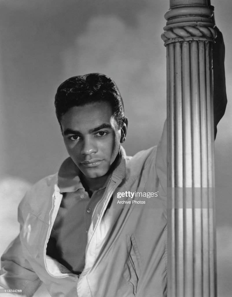 Portrait of American singer Johnny Mathis holding on to a lamp post circa 1958