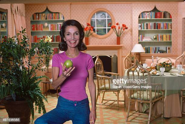 Portrait of American socialite Lee Radziwill as she poses with an apple in her dining room March 1976