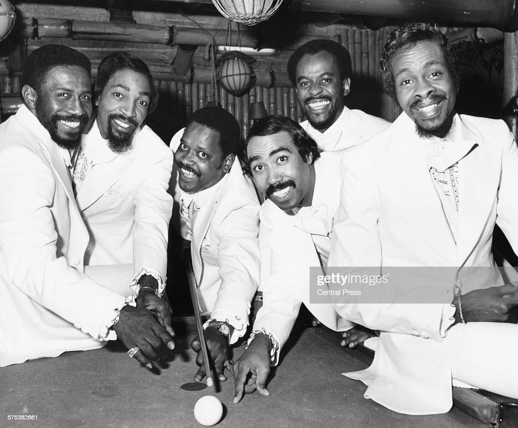Portrait of American soul group 'The Tymes' sitting around a pool table during their tour of Britain London February 24th 1975
