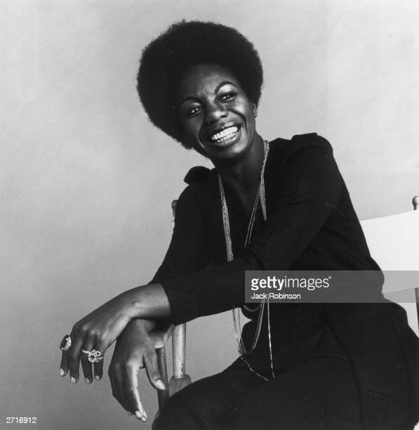 Portrait of American vocalist Nina Simone sitting in a white director's chair and smiling
