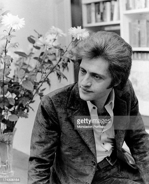 Portrait of Americanborn French singer Joe Dassin beside a flowerpot Paris 1970s