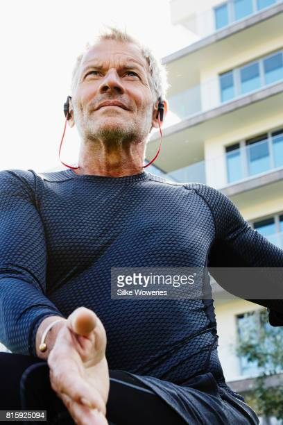 portrait of an active content senior man exercising in a park listening to a podcast