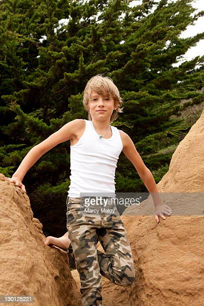 Portrait of an adolescent boy climbing on rocks.