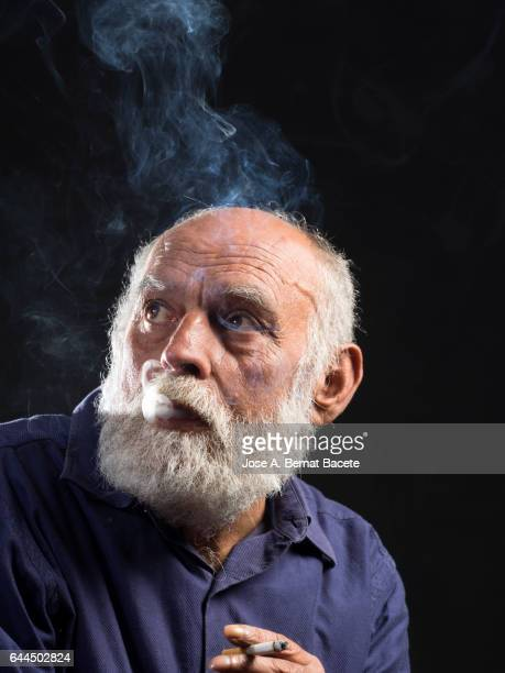 Portrait of an adult man with white beard surrounded with smoke, with a cigarette in his hand