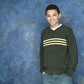 portrait of an african american boy in green sweater as he puts his hands in his pockets and smiles