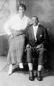Portrait of an African American husband and wife the husband is sitting in a chair in front of a decorative wall mural and the wife is sitting on one...