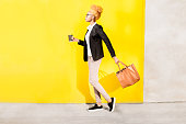 Full body portrait of an african business lady in casual suit walking with bag on the yellow wall background