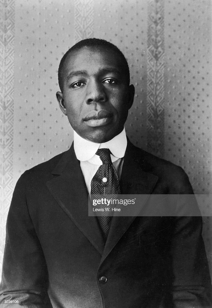 A portrait of an African-American man wearing a suit, tie and tie pin against a wallpaper background.