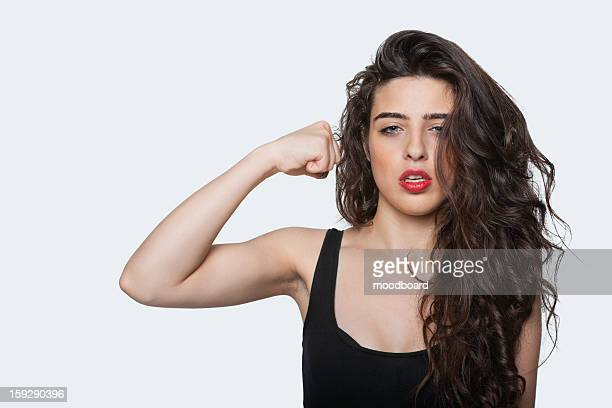Portrait of an aggressive woman with punching gesture over gray background
