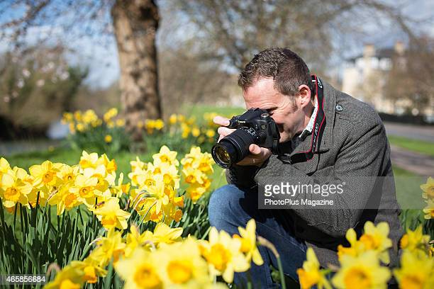 Portrait of an amateur photographer with a Canon EOS 70D digital SLR taking pictures of daffodils taken on March 4 2014