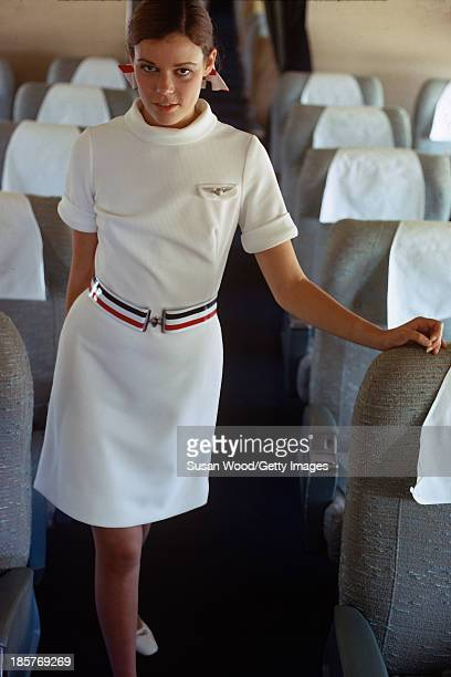 Portrait of an American Airlines air stewardess as she poses in uniform in the aisle of an airplane September 1967 The photo was taken as part of a...