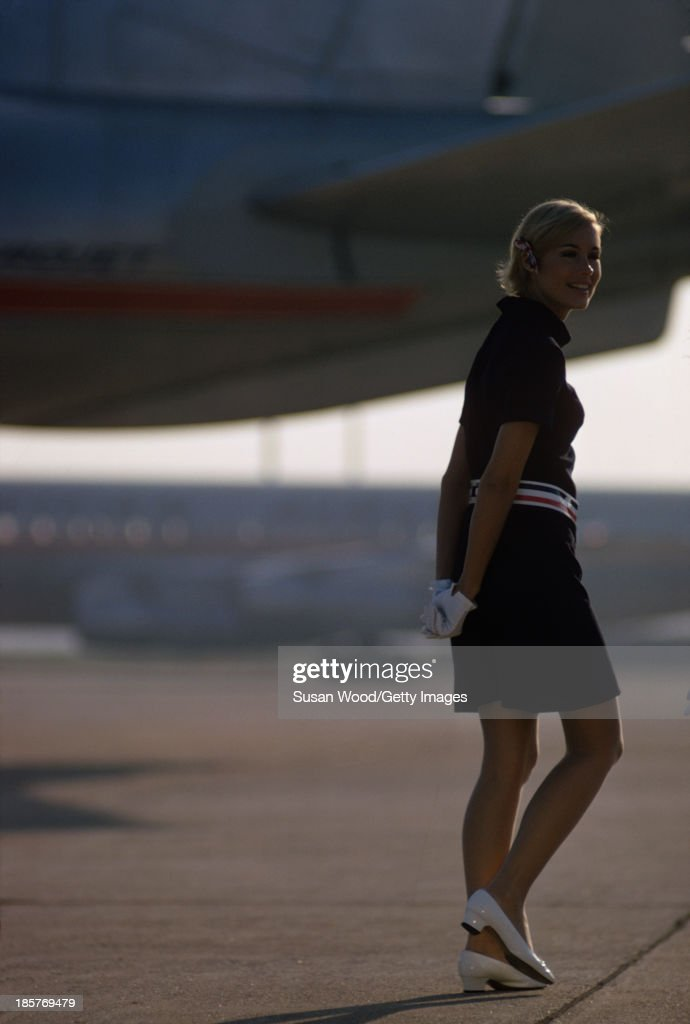 Portrait of an American Airlines air stewardess as she poses, in uniform, on an airport tarmac, September 1967. The photo was taken as part of a billboard ad campaign for the airline.