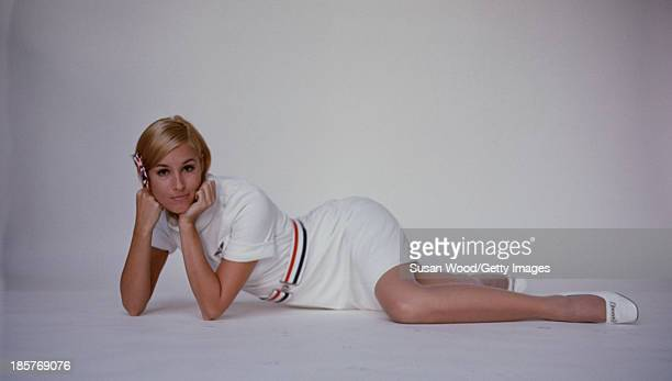 Portrait of an American Airlines air stewardess in uniform as she lies on the floor and poses against a white backdrop September 1967 The photo was...