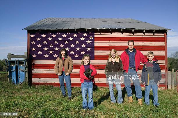 Portrait of an American family standing in front of a barn with the United States flag on the side.