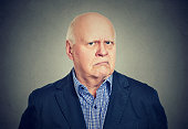 Portrait of an angry, grumpy senior business man, isolated on gray background