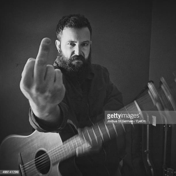 Portrait of an angry mid adult man showing middle finger