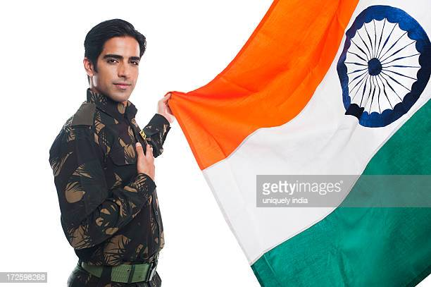 Portrait of an army soldier standing with a hand on his heart while holding Indian flag