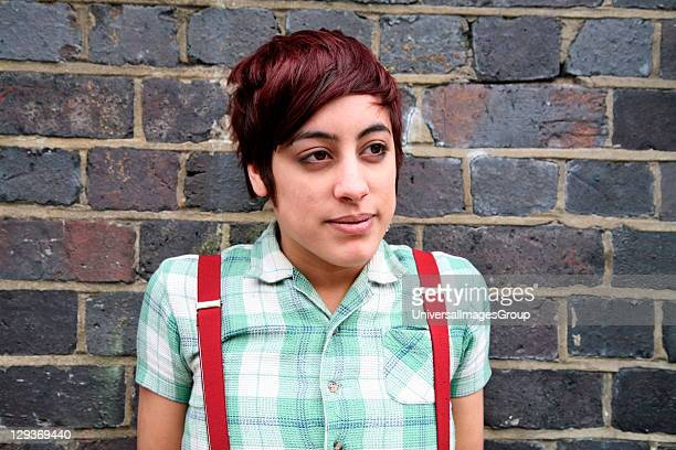 Portrait of an Asian girl wearing a checked shirt and braces Brick Lane London UK 2006