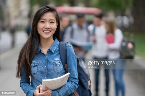 笑みを浮かべてカメラを見て通りアジア学生の肖像画