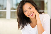 Portrait of an Asian woman laughing and smiling.