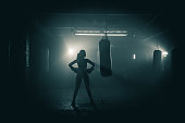 Young woman  boxer with dramatic lighting and a grunge image technique