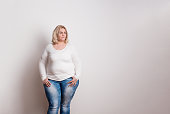Portrait of an attractive blond overweight woman in studio on a white background. Copy space.