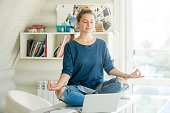 Portrait of an attractive woman on the working table. Lotus pose. Motivation photo