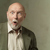 portrait of an elderly bearded caucasian man in a olive green suit as he looks shocked and surprised