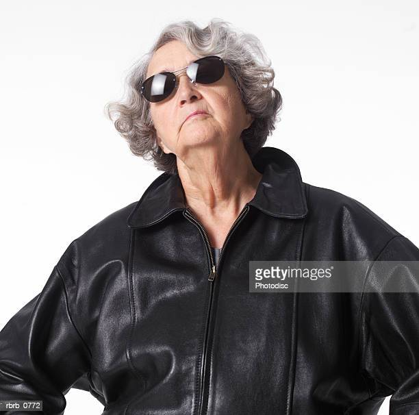 portrait of an elderly caucasian woman in a leather jacket and sunglasses as she throws her head back confidently