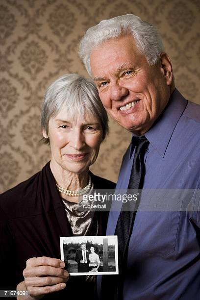 Portrait of an elderly couple showing a photograph