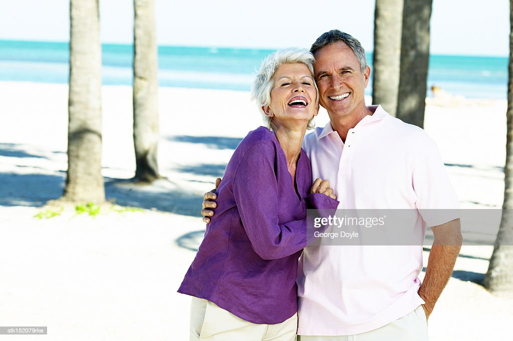 Portrait of an elderly couple smiling standing at the beach