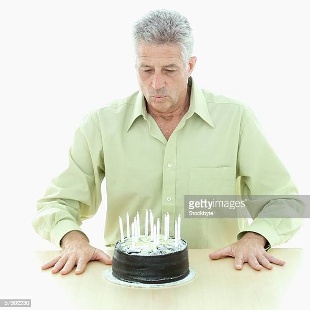 Portrait of an elderly man blowing candles out on birthday cake