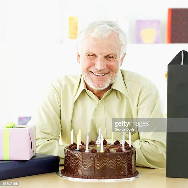 Portrait of an elderly man sitting with a birthday cake
