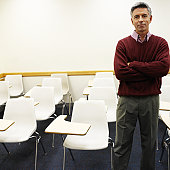 portrait of an elderly man standing in a classroom
