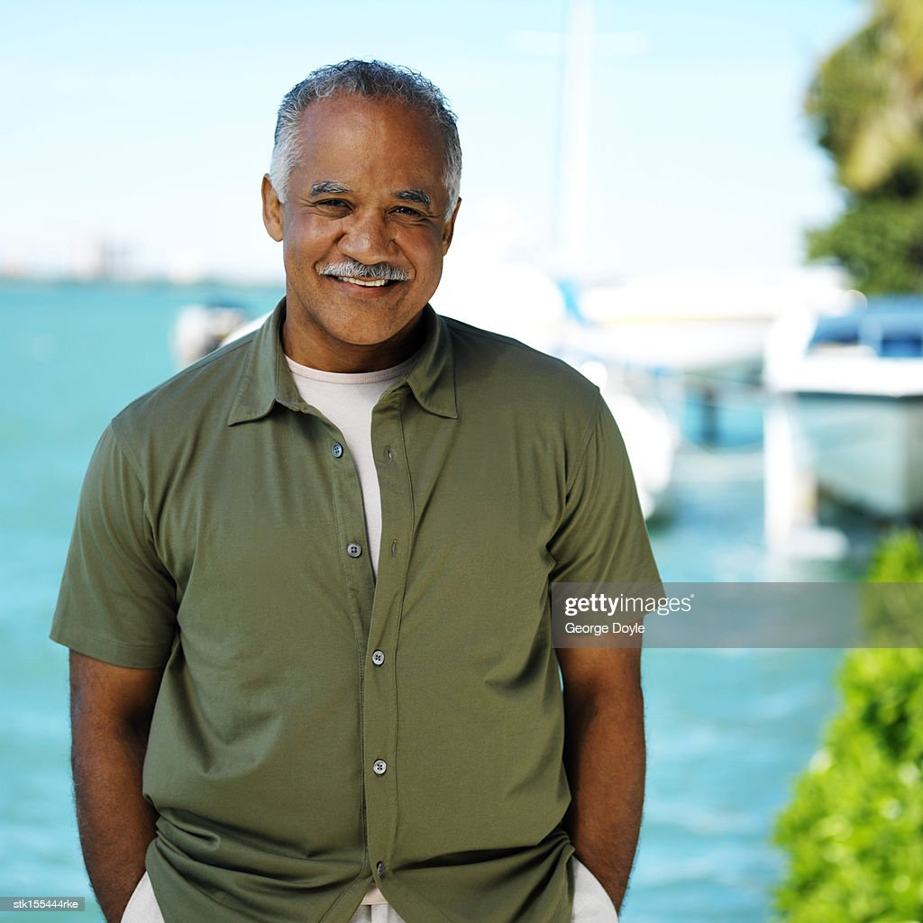 Portrait of an elderly man standing with his hands in his pockets smiling : Stock Photo