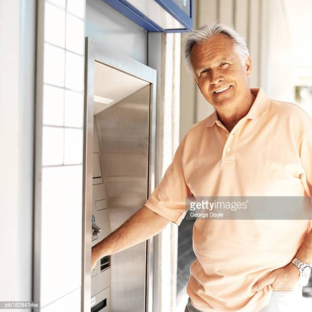 portrait of an elderly man withdrawing money from an atm