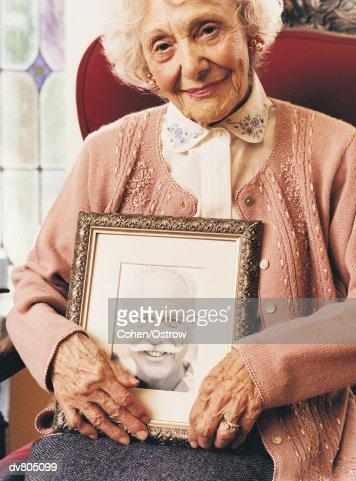 Portrait of an Elderly Widow Holding a Photograph of her Dead Husband