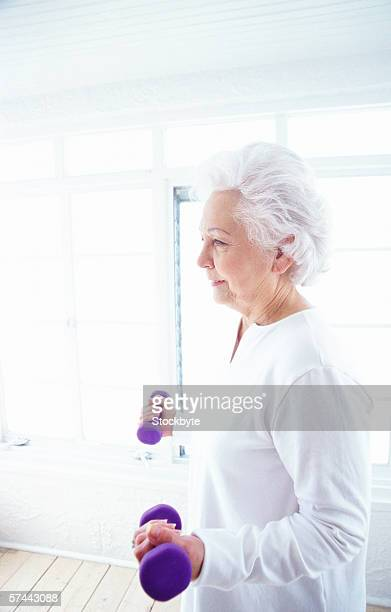 portrait of an elderly woman exercising with dumbbells